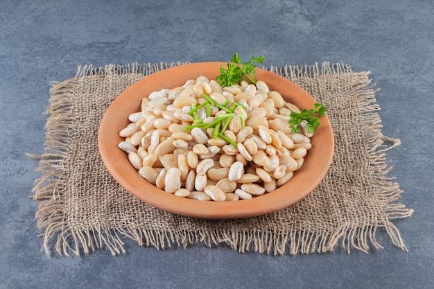 Feijão branco em um prato no guardanapo de estopa na superfície do mármore