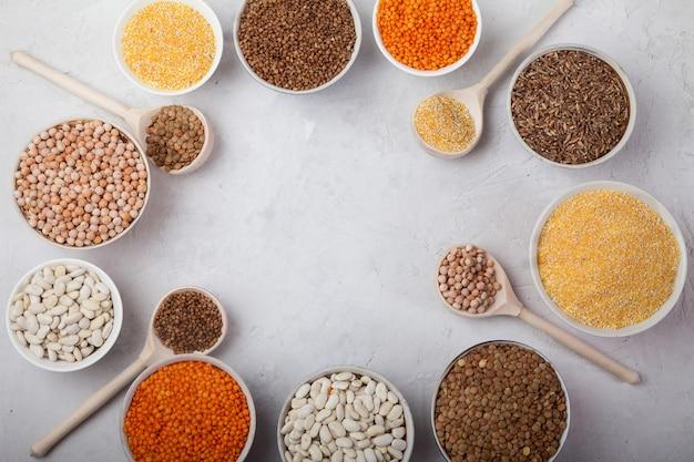 Feijão branco, ervilhas, lentilhas, trigo mourisco, copos de grãos de milho e colheres de madeira sobre um fundo branco