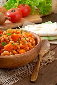 Feijão branco estufado e abóbora fatiada em molho de tomate