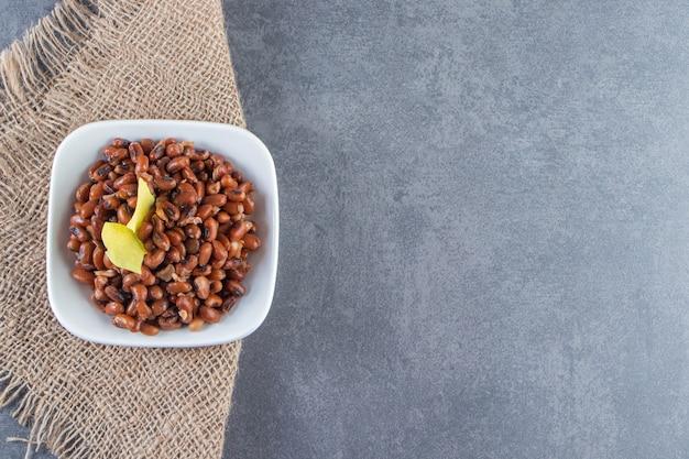 Feijão cru e folhas de lasanha em uma tigela no guardanapo de estopa, sobre o fundo azul.