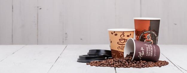 Feijão de café com copo de papel com fundo de madeira