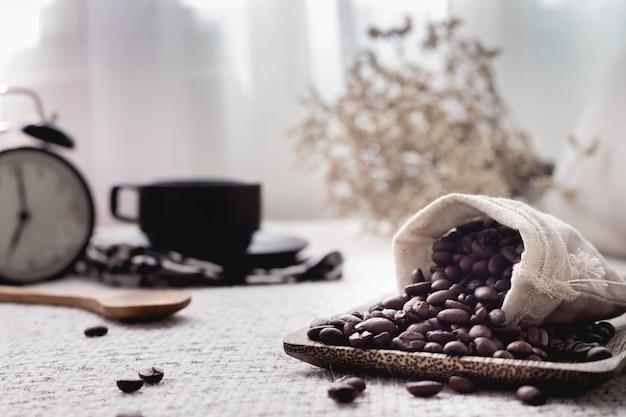 Feijão de café e copo de café na tabela.