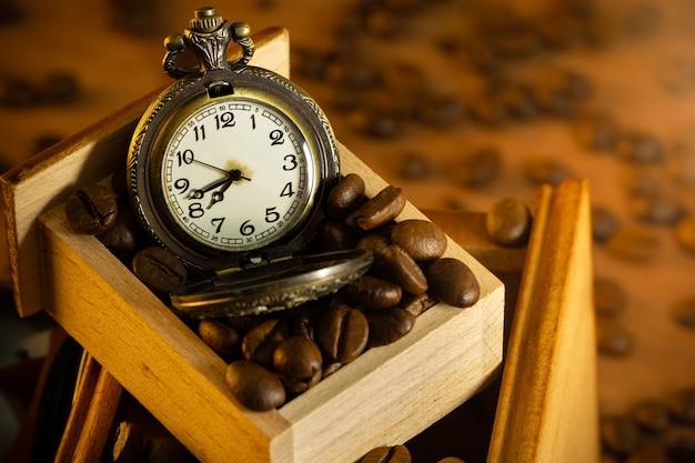Feijão de café e relógio de bolso no moedor manual na mesa