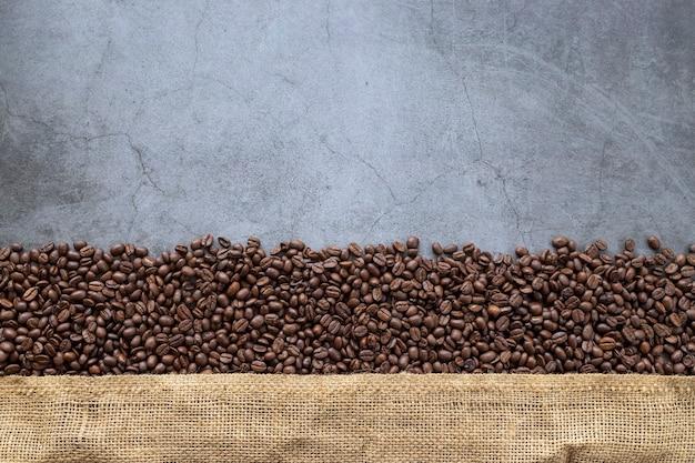 Feijão de café e saco em fundo de cimento velho
