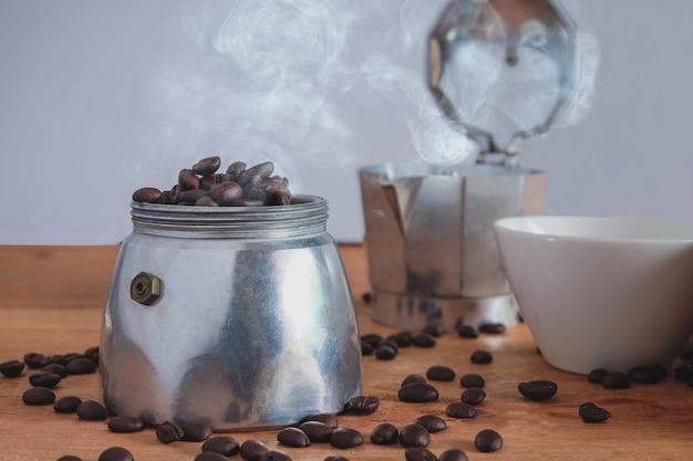Feijão de café fresco na cafeteira de pote moka na mesa.