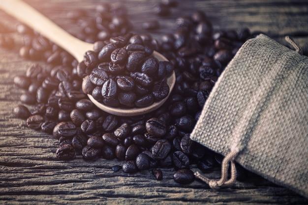 Feijão de café na colher e saco no fundo de madeira