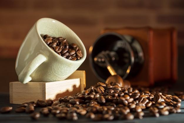 Feijão de café no copo branco e moedor de café na mesa de madeira. conceito café da manhã ou café na manhã.