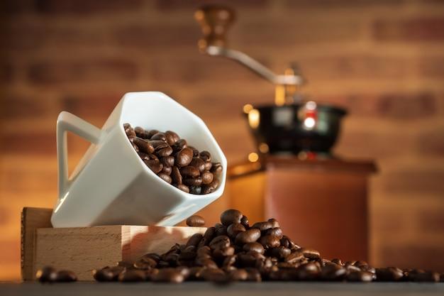 Feijão de café no copo branco e moedor de café na mesa de madeira.