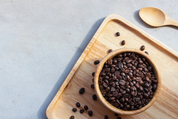 Feijão de café no copo de madeira no fundo da mesa