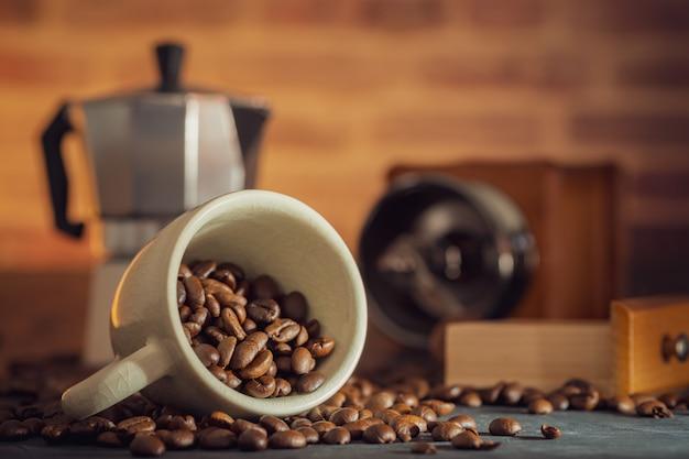 Feijão de café no copo e no moedor de café brancos na tabela de madeira. café da manhã do conceito ou tempo do café na manhã.