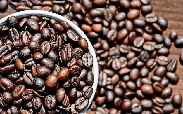 Feijão de café no copo na mesa de madeira