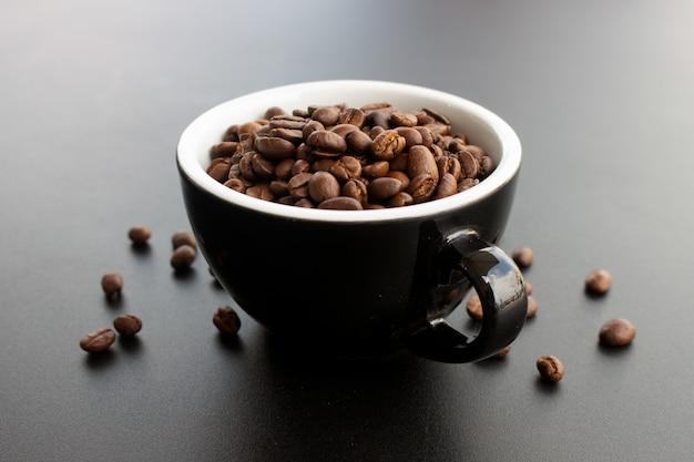 Feijão de café no copo no fundo preto