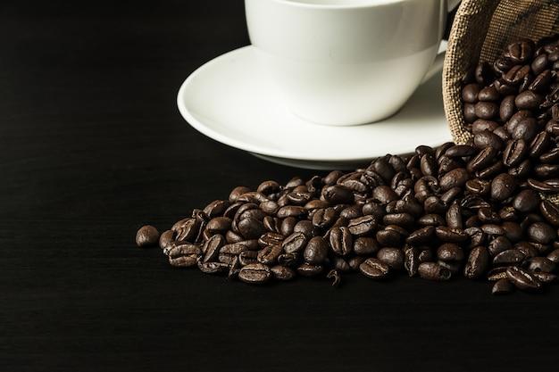 Feijão de café no fundo de madeira preto