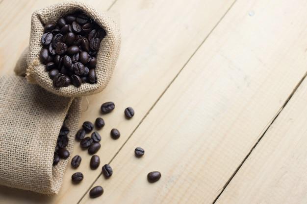 Feijão de café no saco na tabela de madeira. visão de alto ângulo