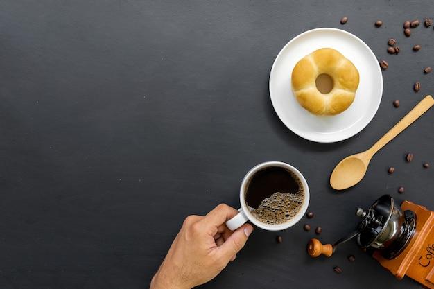 Feijão de donuts de café quente e moedor manual no fundo preto da mesa