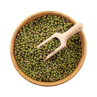 Feijão de mung cru ou feijão verde em uma tigela de madeira isolada no fundo branco
