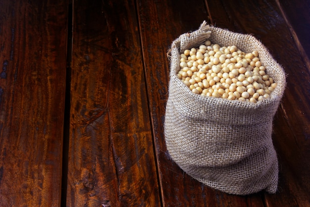 Feijão de soja cru e fresco no saco de tecido rústico na mesa de madeira