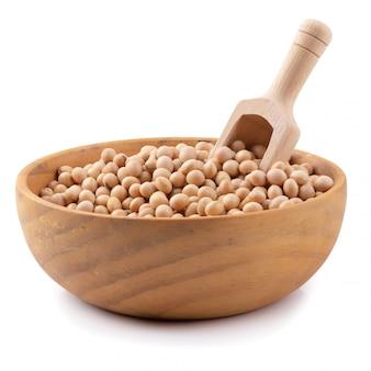 Feijão de soja em uma tigela de madeira, isolada no fundo branco