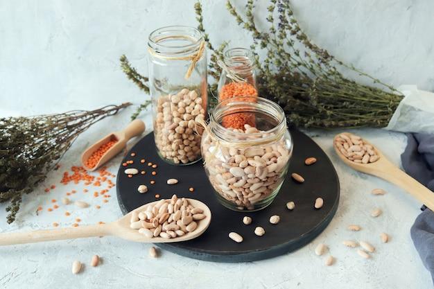 Feijão, lentilhas de grão de bico e ervas secas na mesa da cozinha produtos naturais orgânicos