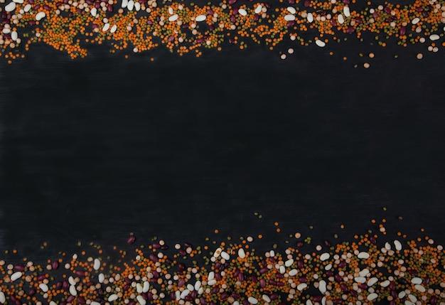 Feijão, lentilhas, feijão mungo, ervilhas são dispostos sobre um fundo preto de madeira acima e abaixo