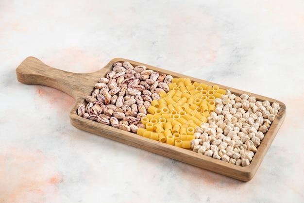 Feijão, macarrão e grão de bico na bandeja de madeira.
