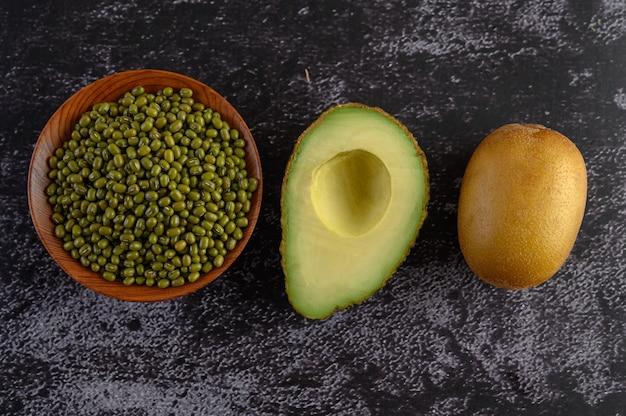 Feijão mungo, abacate e kiwi em um piso de cimento preto.