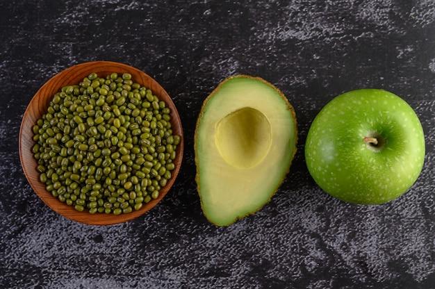 Feijão mungo, abacate e maçã em um piso de cimento preto.