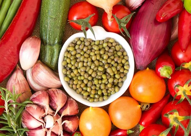 Feijão mungo orgânico seco na tigela entre vista superior de vegetais crus