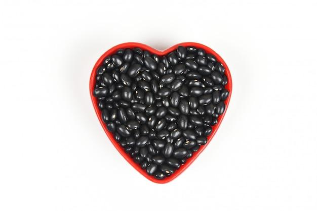 Feijão preto em placa de coração vermelho / grãos integrais de cereais de semente de feijão preto, isolados no fundo branco