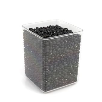 Feijão preto em uma panela transparente em fundo branco.