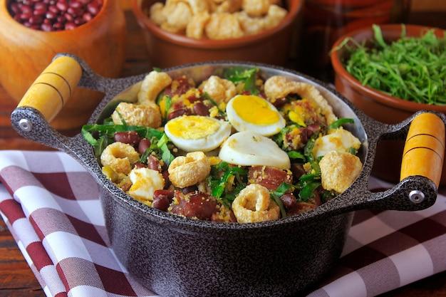 Feijão tropeiro prato típico da culinária brasileira, feita com feijão, bacon, linguiça, couve, ovos, mesa de madeira rústica.