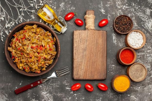 Feijão verde com tomate o apetitoso feijão verde e tomate ao lado do garfo especiarias coloridas tomate garrafa de óleo e a tábua na mesa