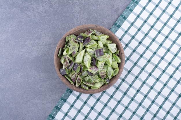 Feijão verde dentro de um recipiente ou prato em fundo de concreto.