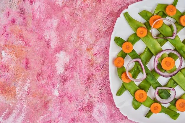 Feijão verde e cenoura em um prato branco.