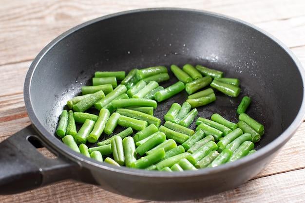 Feijão verde em uma frigideira em um fundo de madeira.