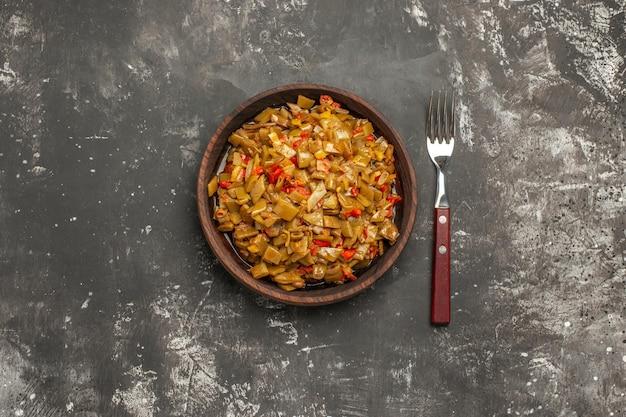 Feijão verde feijão verde e tomate na tigela de madeira ao lado do garfo na mesa escura