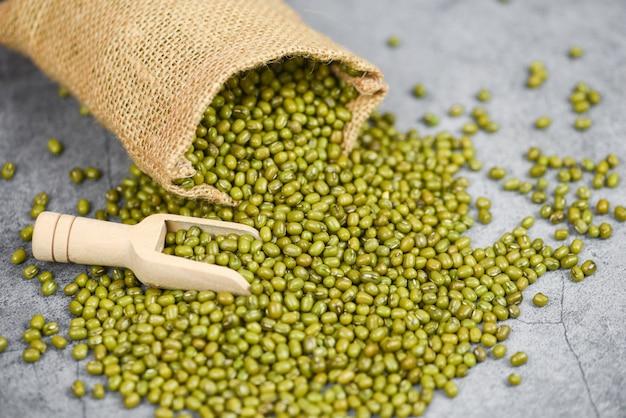 Feijão verde no saco com colher de madeira - grãos integrais de cereais de sementes de feijão mungo