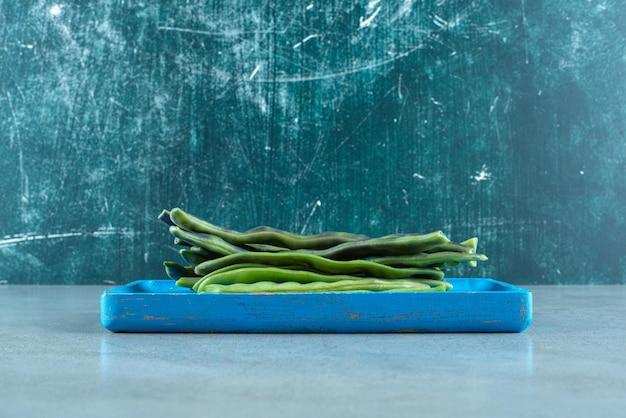 Feijão verde orgânico na placa azul.
