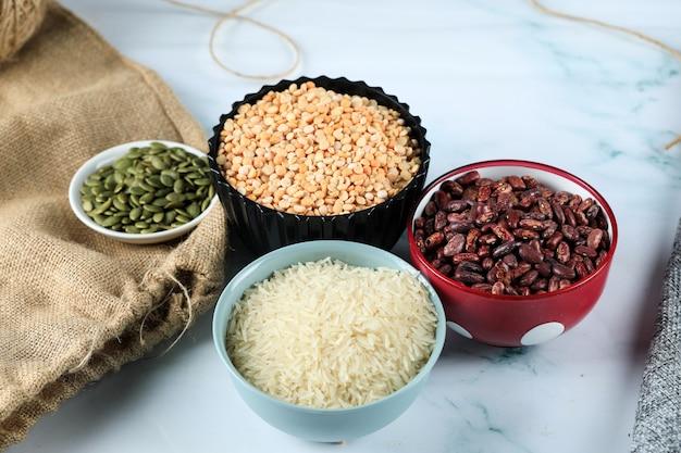 Feijão vermelho, arroz e ervilhas em tigelas coloridas