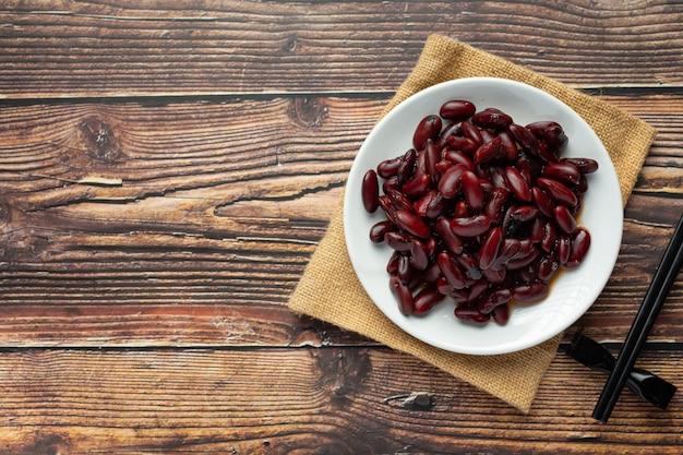 Feijão vermelho cozido em prato branco lugar no chão de madeira