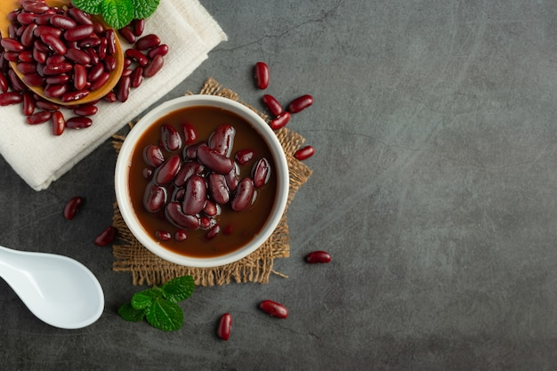 Feijão vermelho cozido em uma tigela branca, coloque no chão escuro