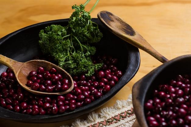 Feijão vermelho cru em placas pretas, tábua de cortar e acompanhado de salsa