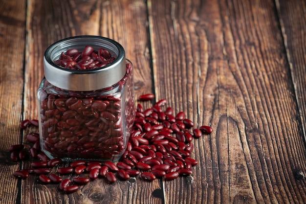 Feijão vermelho em um pequeno frasco colocado no chão de madeira