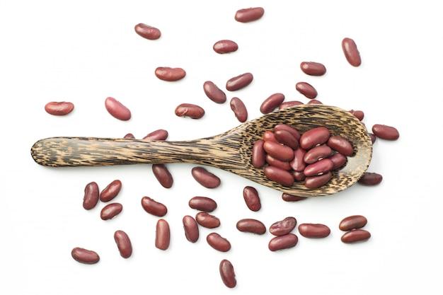 Feijão vermelho em uma colher de pau isolar em branco