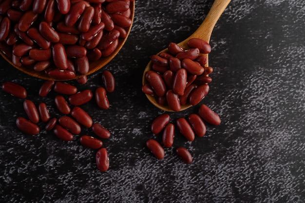Feijão vermelho em uma tigela de madeira e colher de pau no chão de cimento preto.