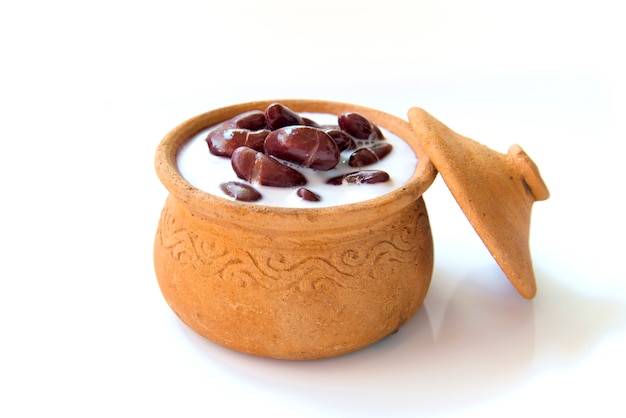 Feijão vermelho tailandês da sobremesa no leite de coco com o potenciômetro de argila isolado no fundo branco