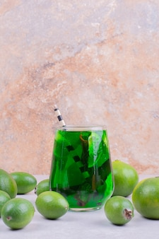 Feijoa e tangerina com um copo de suco verde.
