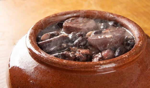 Feijoada brasileira, pequena tigela de barro com uma deliciosa feijoada brasileira em madeira rústica