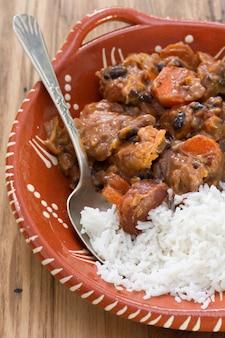 Feijoada de prato típico português com arroz em uma tigela de cerâmica na mesa de madeira marrom