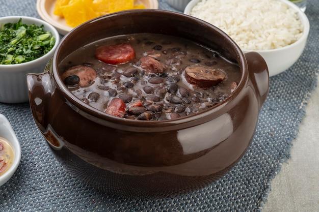Feijoada tradicional brasileira com arroz, laranja, couve e pimenta.